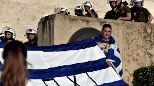 """Demonstrant håller upp flagga med ordet """"nej"""" på grekiska"""