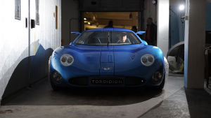 En låg blå sportbil rullar fram inne i en byggnad.En man sitter bakom ratten inne bilen.