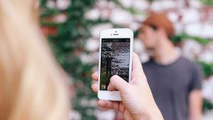 flicka fotograferar pojke med smarttelefon