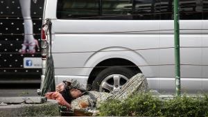 Hemlös kvinna sover på gatan i Thailands huvudstad Bangkok 25.2. 2015.