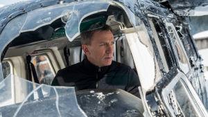 Bond istuu lentokoneessa, jonka ikkuna on rikki.