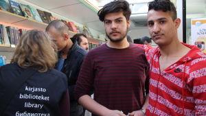 Motaz och Hussein i bokbussen i Knäcktbro i Esbo.