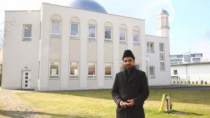 mies moskeijan edessä hattu päässä