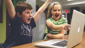 två blada barn sitter vid en dator i skolan