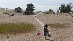 Familj på väg till sandstrand.