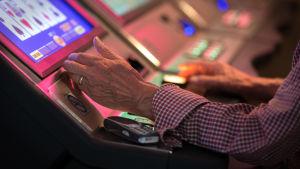 Lähikuva vanhan miehen käsistä pelaamassa rahapelejä Casino Helsingissä.