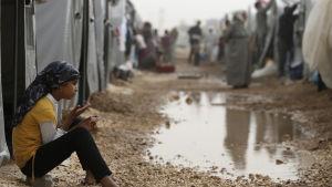 En syrisk flicka sitter utanför sitt tält på ett flyktingläger i Sanliurfa i Turkiet.