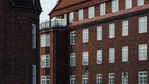 Ett brunt tegelhöghus med rött tak och vita fönsterkarmar.