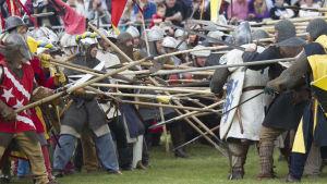 Historiskt återskapandet av slaget vid Bannockburn år 2014 under evenemanget Bannockburn Live. Skådespelare klädda i medeltida kostymer med medeltida vapen.
