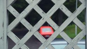 Sliten målarfärg på staket, i bakgrunden en gammal röd bil.