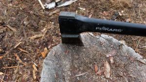"""Kirves. """"Fiskars""""-merkkinen halkaisukirves. Halkaisupölkky. Metsätyöt. Työkalu.  Esine. Kirveet, halkaisukirveet, halonhakkuu."""