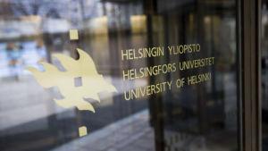 Helsingfors universitets logo på en dörr till en byggnad.