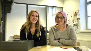 Josefine Sundblom och Matilda Skrifvars sitter vid ett bord där de har ett kassaskrin, papper, penna och en telefon.