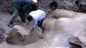 Några män gräver fram en staty som tros vara Ramses II.