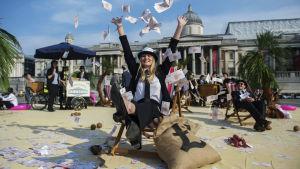 Aktivist sitter på stol och kastar leksakspengar i luften.