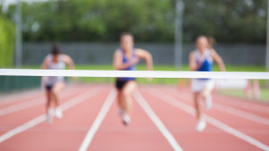 Tre unga löpare på en bana springer mot mållinjen.