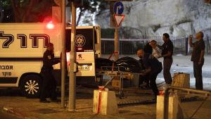 Räddningspersonal för bort kroppen av en av de tre palestinier som angrep poliser i Jerusalem