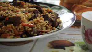 En gryta med ris, kött och grönsaker på en tallrik. Bredvid tallriken står en tekopp. I bakgrunen syns ett fat med ljust bröd.