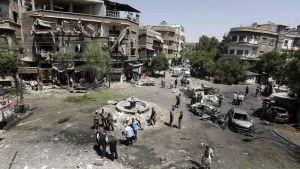 Människor besöker Tahrirtorgsdistriktet omgivet av trasiga hus där en av tre bilbomber exploderat tidigare under dagen. Åtminstone åtta människor miste livet och ett tiotal skadades i dådet den 2 juli 2017.