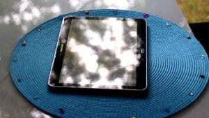 En pekdator på ett bord i solen.
