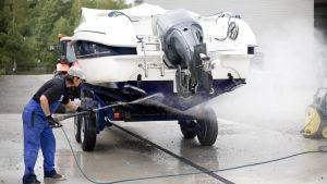 En man tvättar båtbotten med vatten.