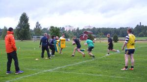 rugbyspelare på gräsplan. Några springer mot dynor som andra håller upp.
