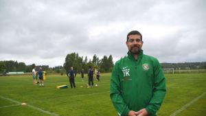 John king står framför gräsplan med spelare.