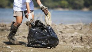 Person samlar upp plastsavfall i en sopsäck på skräpig strand.