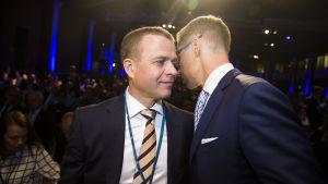 Petteri Orpo i randig slips lyssnar då Alexander Stubb talar i hans öra under Samlingpartiets partikongress i Villmanstrand.