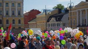 Ballonger i olika färger tillsammns med människor på Senatstorget i Helsingfors under Helsingfors Pride 2016.