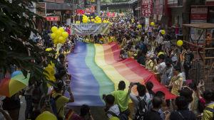 Prideparad i Hongkong år 2015. Folkmassan håller upp en jättelik regnbågsflagga. Överallt syns gula ballonger.