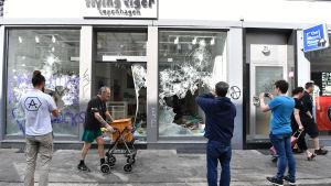 Några personer fotograferar en affär som förstörts under G20-protesterna.