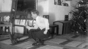 En man lyfter en stol med sin ena hand samtidigt som han är på huk med ena benet framåt. Bilden är tagen 1936 i Kulla, Strömfors.