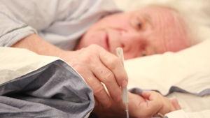 Man i sängen tittar på febertermometer.