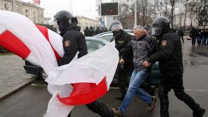 Kravallpolis griper demonstranter i Minsk. En stor flagga fladdrar i bildens förgrund.