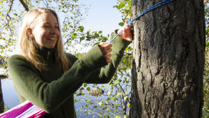 Hanna Enlund spänner upp sin hängmatta.