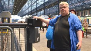 Man håller i en radio på järnvägsstationen