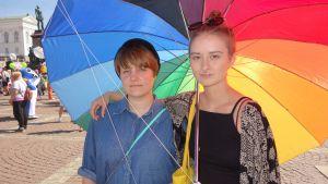 Riikka Laaksoharju (till vänster) och Vilma Aro håller om varandra under ett regnbågsparaply.