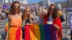 Ninni Pöysti, Moa Pöysti, Saga Pöysti, Cecilia Degerlund håller upp regnbågsflaggor och säger att alla ska få älska den man vill.