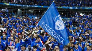 Isländska supportrar med en Lars Lagerbäck-flagga.