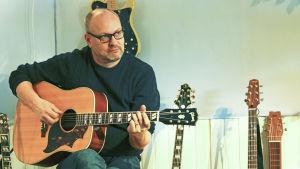 Niklas Nylund spelar gitarr i sin studio i Borgå.