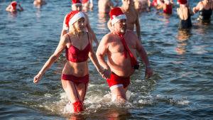 Människor i tomteinspirerad badutstyrsel deltar i ett traditionellt evenemang i Orankesee i Berlin.