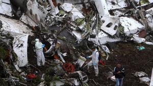 Räddningsmanskap klädda i vita skyddsoveraller står mitt i vraket efter planet som störtade utanför Medellin i Colombia.