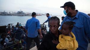 En kvinna och ett barn förs i land av Libyens kustbevakning.