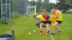rugbyspelare på plan. En man i rött försöker ta bollen bakifrån av en man i gult.