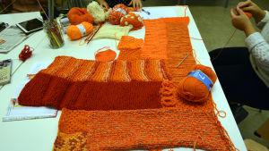 Ett lapptäcke som inte är klart, det är olika stickningar i olika orange nyanser som är ihopsydda