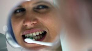En tjej som borstar tänderna.