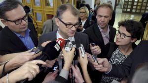 Statsminister Juha Sipilä omringad av journalister.