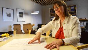 Biblioteksdirektör Margareta Kull-Poutanen granskar ritningarna för det nya biblioteket.