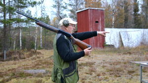 Jägaren och skytten Henrik Gullans står i profil, i händerna håller han ett halvautomatgevär och han har hörlurar på huvudet.
